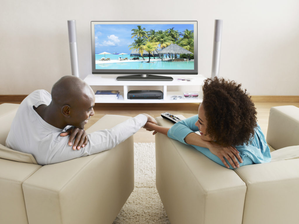 75593112 A couple holding hands in front of a television