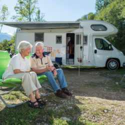 Senior couple having fun camping with camper van