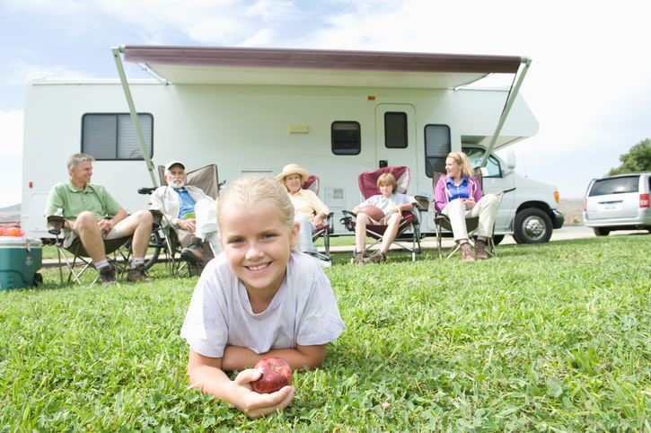 Cute little girl lying on grass family sitting outside RV
