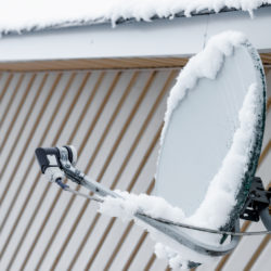 snow covered satellite dish on the roof
