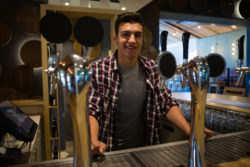 Young male bar owner standing behind a bar