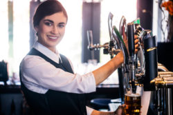 female bartender bar owner pouring a pint