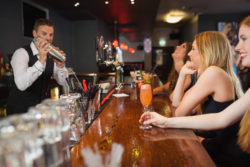 male bartender making drinks for pretty ladies