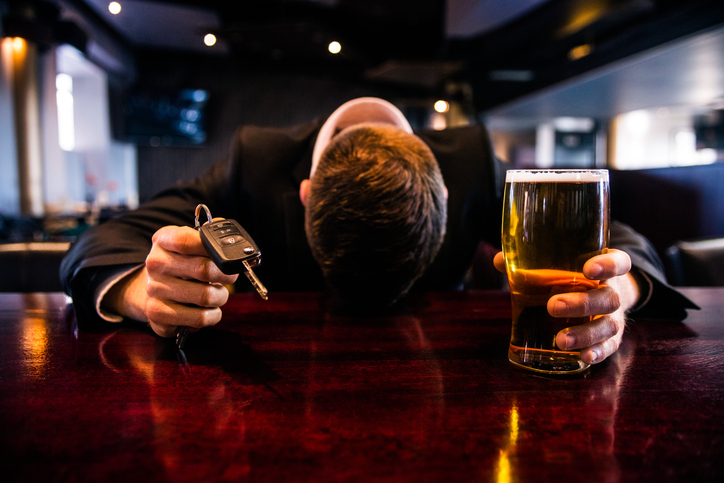 Drunk man holding a beer and car keys