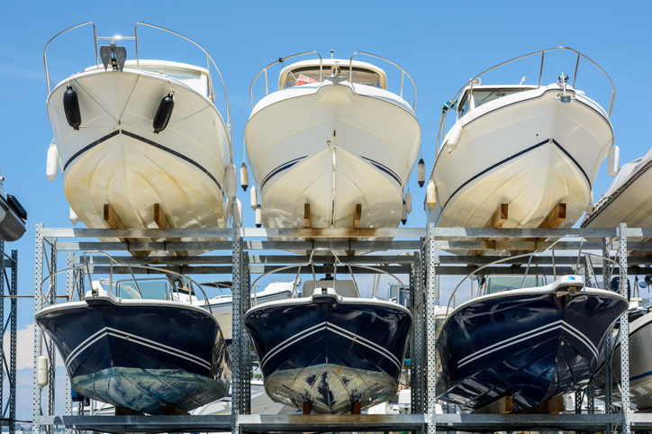 View from below of the hulls of motorboats racked one above another on two levels in a dry rack boat storage facility against blue sky.