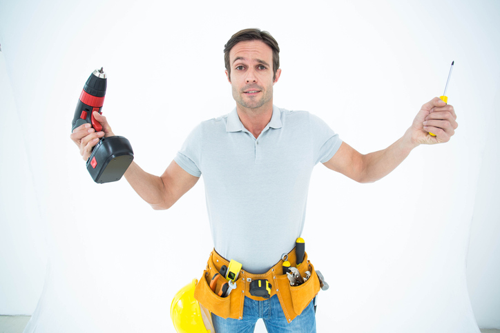Confused technician holding screwdriver and drill machine