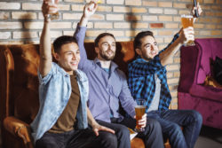 Friendship, sports and entertainment concept - happy male friends with beer watching tv at home promotion for bar owners directv