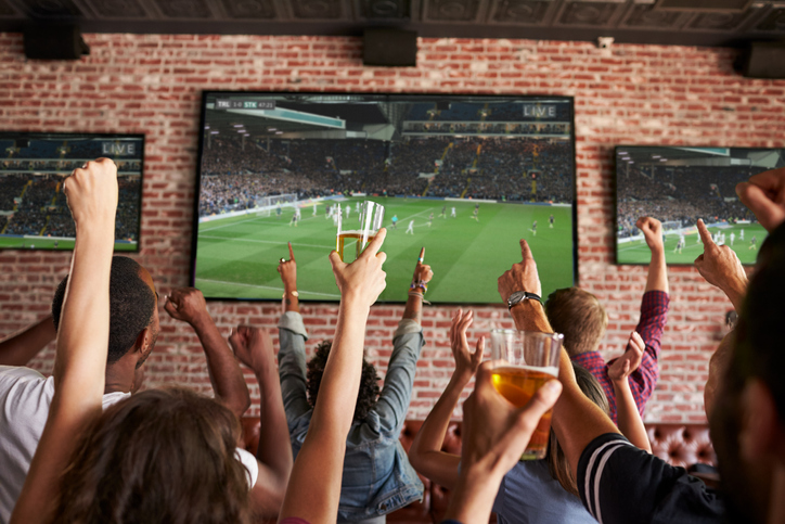 Rear View Of Friends Watching Game In Sports Bar On Screens